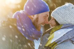Happy Young Couple in Winter Park laughing and having fun. Family Outdoors. Stock Photo