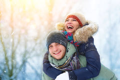 Happy Young Couple in Winter Park laughing and having fun. Family Outdoors. Royalty Free Stock Photography