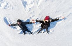 Happy young couple in winter park lying on snow. Top view stock photography
