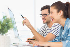 Happy young couple working on computer in an office Stock Photos