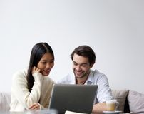 Happy young couple working on laptop at home Royalty Free Stock Photos