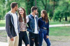 Happy young couples spend fun time outdoors. Love and friendship. Happy young couples spend fun time. Focus on beautiful women with long hair, she smiling and Royalty Free Stock Photos