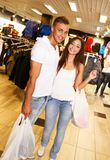 Happy young couples in sportswear store Stock Photos