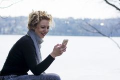 Happy young curly blond woman sitting by the river and typing on Stock Images