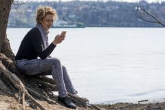 Happy young curly blond woman sitting by the river and typing on Royalty Free Stock Photo