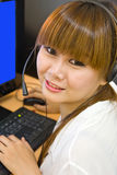 Happy young customer service. Operator girl wearing headset, working on computer, smiling Royalty Free Stock Photos