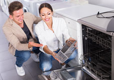 Happy young customers choosing new dish washing machine Royalty Free Stock Photos