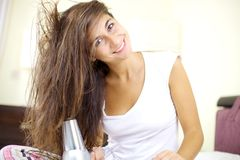 Happy young cute girl hairdrying long hair Stock Photos