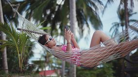Happy young cute girl lying down in outdoor swing bed enjoying sun sunbathing using mobile phone. 1920x1080. Happy beach woman reading sms texting on smartphone stock video