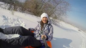 Happy young cute woman is sledding in the mountain through the sun in slow motion on sunny day in winter and recording. Happy young pretty woman is sledding in stock footage