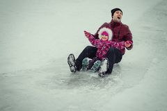 Dad rolling with daughter on sled in winter park Royalty Free Stock Images