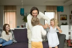 Happy young dad playing having fun with kids at home. Happy young dad having fun with kids at home, smiling daddy playing with children son and daughter in Royalty Free Stock Photo