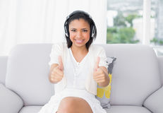 Happy young dark haired woman in white clothes listening to music and giving thumbs up Stock Photography