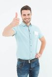 Happy young delivery man gesturing thumbs up Stock Image