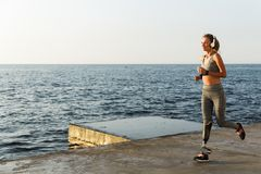Happy young disabled woman with prosthetic leg running. Outdoor at the beach stock photo