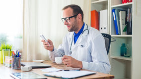 Happy young doctor sitting behind  desk in his modern office. Stock Images