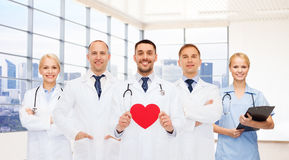 Happy young doctors cardiologists with red heart royalty free stock images