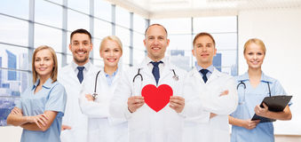 Happy young doctors cardiologists with red heart Royalty Free Stock Image