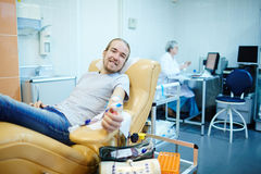 Happy young donor. Young donor giving his blood for people in need royalty free stock photos
