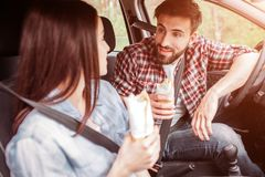 Happy young and dorgeus people are looking at each other. They hane their seatbelts on. Also this cpolpe has tasty stock images
