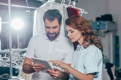 Happy young dry cleaning workers using. Tablet together stock photography