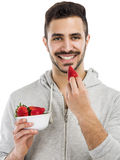 Happy young eating a strawberry Stock Photos