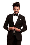 Happy young elegant man in tuxedo buttoning his coat Stock Images