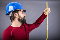 Happy young engineer with hardhat holding a measuring tape Royalty Free Stock Photos