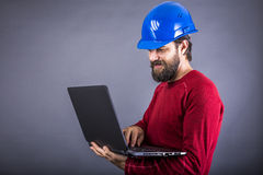 Happy young engineer with hardhat standing while working on his. Laptop over gray background royalty free stock photography