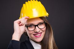 Happy young engineer woman with yellow helmet. Posing friendly on dark background Royalty Free Stock Photos