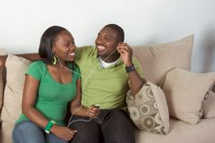 Happy young ethnic black couple listening music stock photo