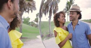 Couple having fun at mirror. Happy young ethnic man and woman standing together and having fun while looking at reflection in the mirror in the park stock video