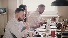 Happy young European business people sit by the table, work together with laptops in modern healthy office, slow motion.