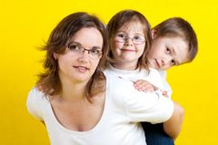 Happy young family. With mother,  daughter and son - yellow background - studio photo Stock Photo