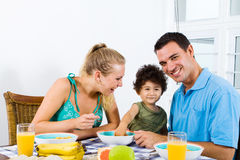 Happy young family. Of two parents and toddler boy at breakfast table Stock Photo