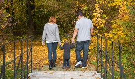 Happy young family in autumn making a walking tour. Royalty Free Stock Photos