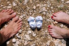 Happy young family awaiting baby, love and happiness. Future mom and dad feet with little unborn baby shoes, closeup. Birth expectation concept. Waiting of stock photo