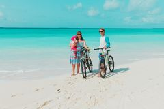Happy young family with baby riding bikes on beach royalty free stock photography