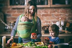 Happy young family, beautiful mother with two children, adorable preschool boy and baby in sling cooking together in a sunny kitch royalty free stock image