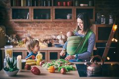 Happy young family, beautiful mother with two children, adorable preschool boy and baby in sling cooking together in a sunny kitch. En. Vintage style stock photos