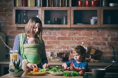 Happy young family, beautiful mother with two children, adorable preschool boy and baby in sling cooking together in a sunny kitch stock image