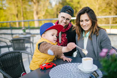 Happy young family in cafe outdoors on sunny day Stock Photography
