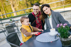 Happy young family in cafe outdoors on sunny day Stock Photo
