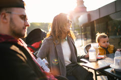Happy young family in cafe outdoors on sunny day Royalty Free Stock Image