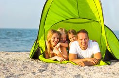 Happy young family camping on the beach Stock Photos