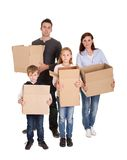 Happy young family carrying boxes Stock Images