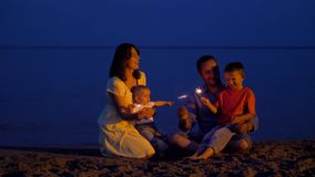 Happy young family celebrating on beach at dusk, kids and parents singing and holding sparklers fireworks stock footage