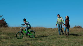 Happy Young Family With a Child On Bike In Autumn stock video footage