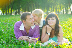 Happy young family with a child lying on the grass Royalty Free Stock Photo