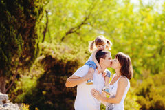 Happy young family with child resting outdoors in summer park Royalty Free Stock Images